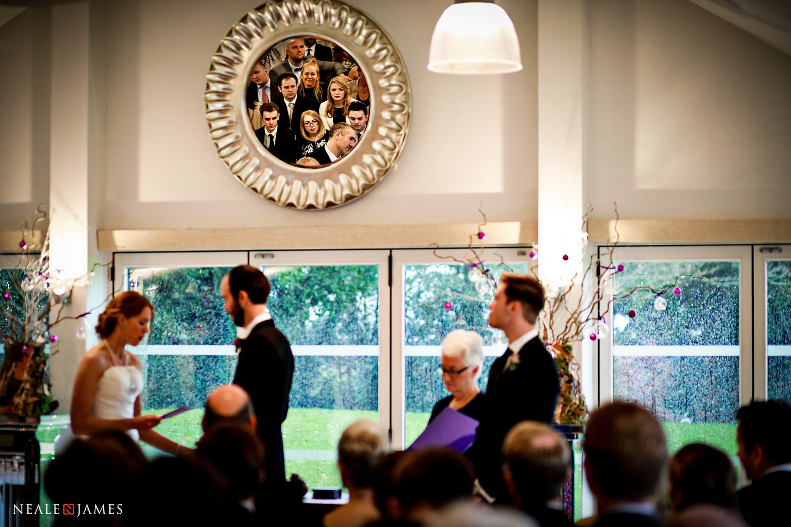 A clever reflection of guests looking on at a bride and groom saying their wedding vows at Wasing Park