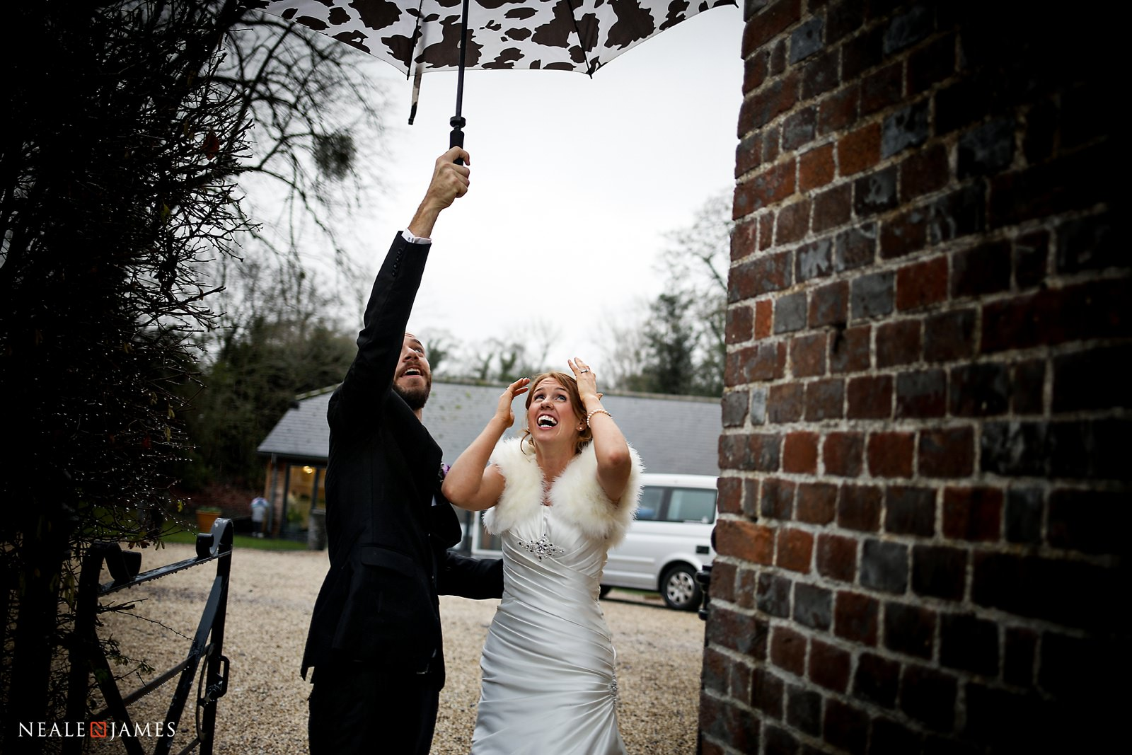 A tricky umbrella manoeuvre is required at Wasing Park as bride and groom head out for their portraits