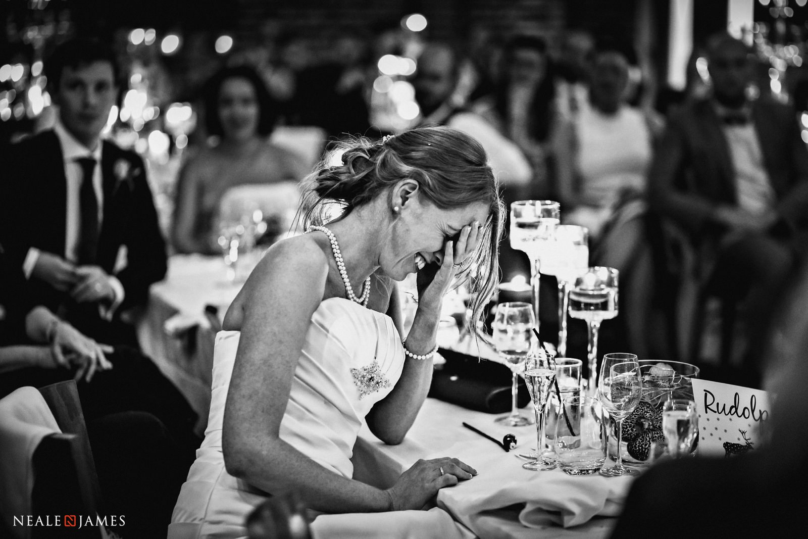 A bride puts her head in her hands and smiles during the speeches at her wedding breakfast at Wasing Park