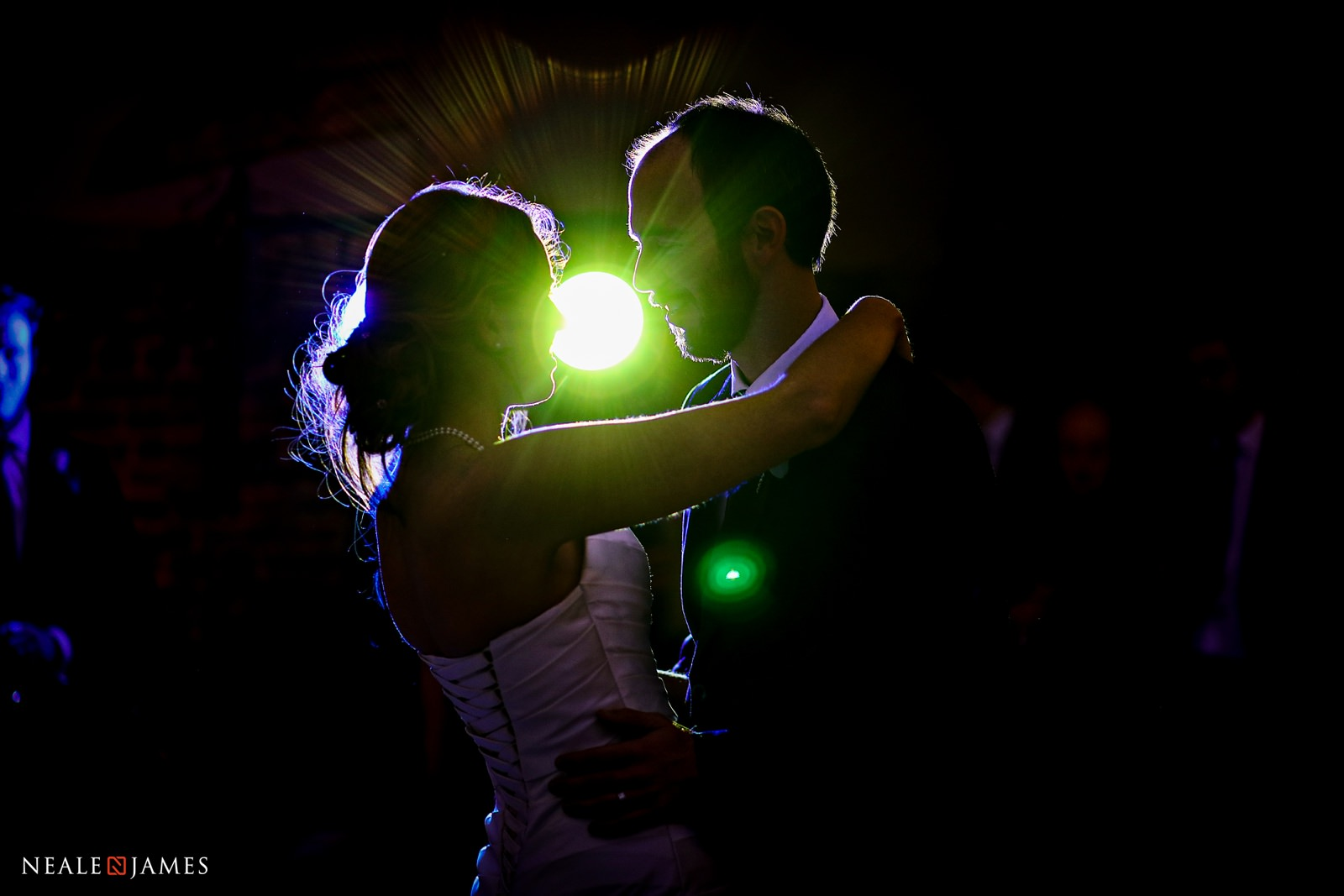 The disco provides green rim lighting for a couple enjoying their first dance at Wasing Park