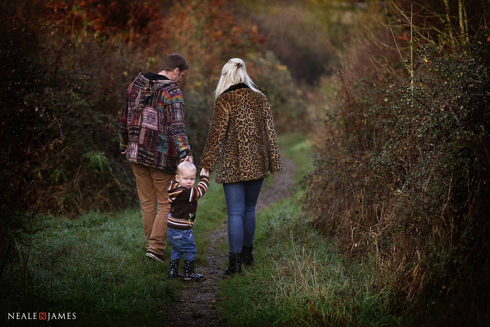 A young boy turns round to look at the camera as he walks hand in hand with his parents through the countryside