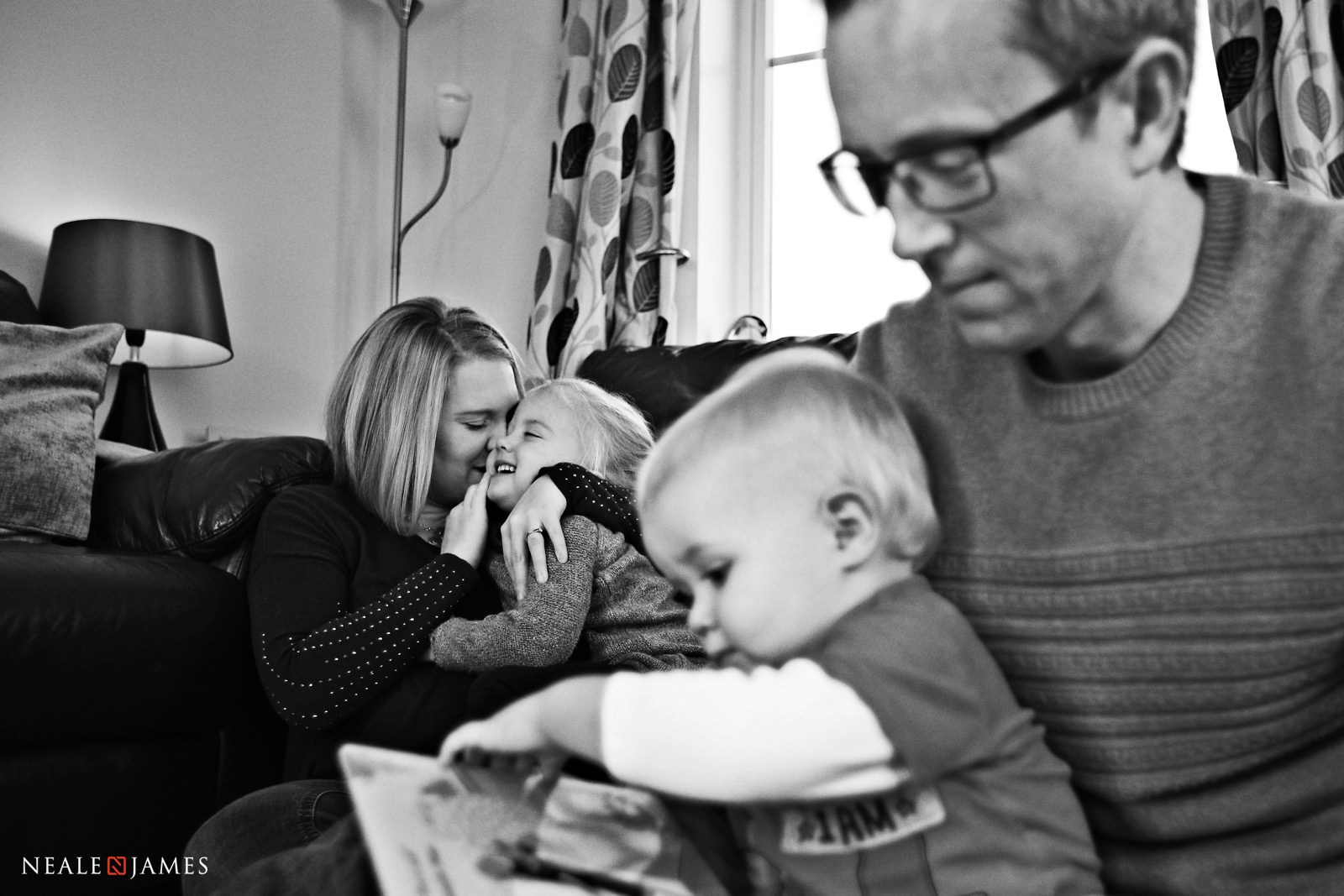 A Mum and her child cuddle in the background while a father and son read together in the foreground of this family photograph