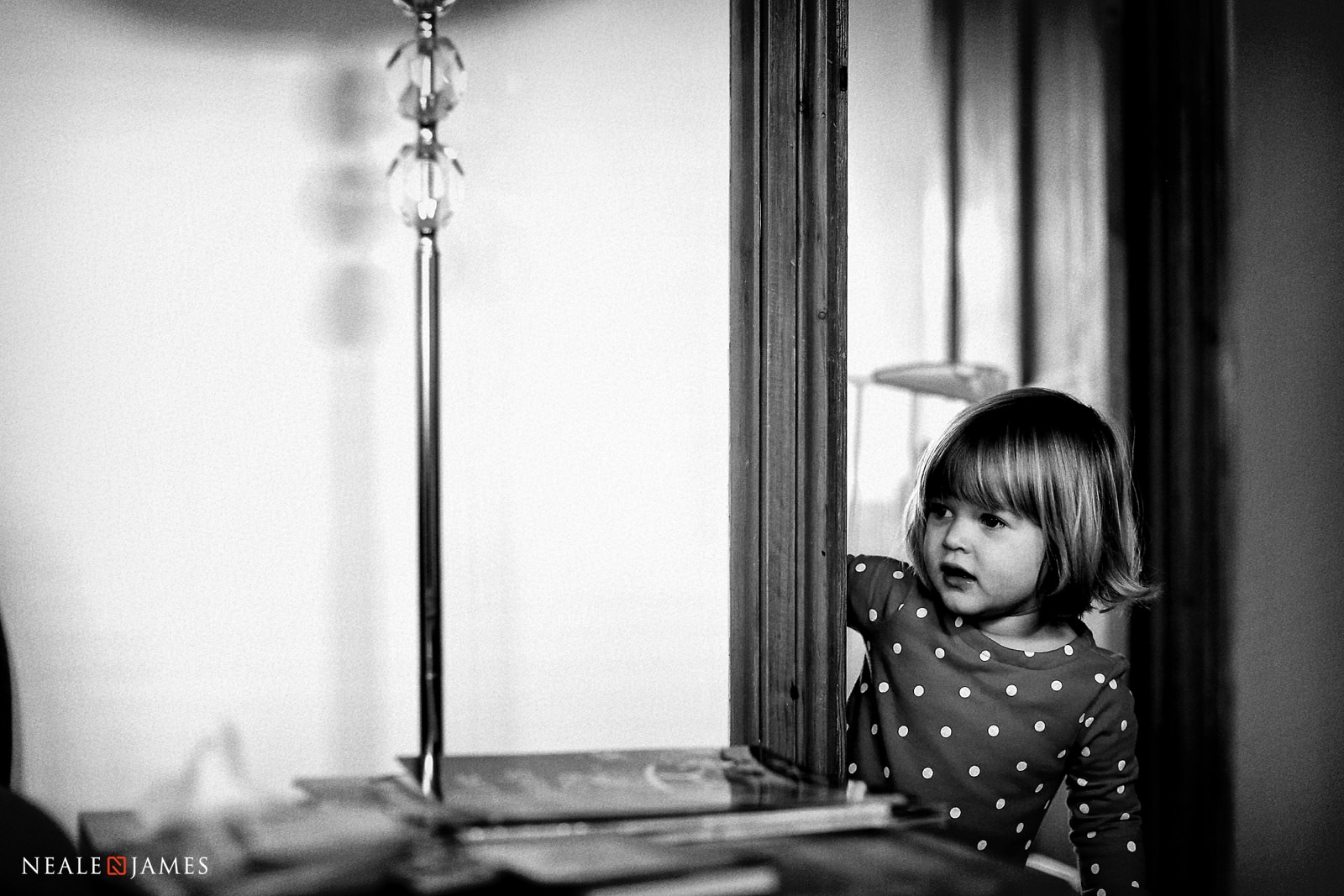 A young girl pokes her head around the corner of the door and looks into a sitting room