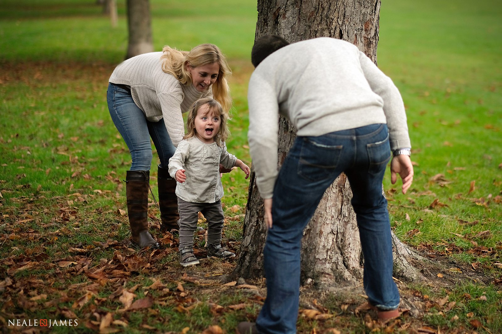 A Dad jumps out from behind a large tree as he plays chase with his daughter in the park