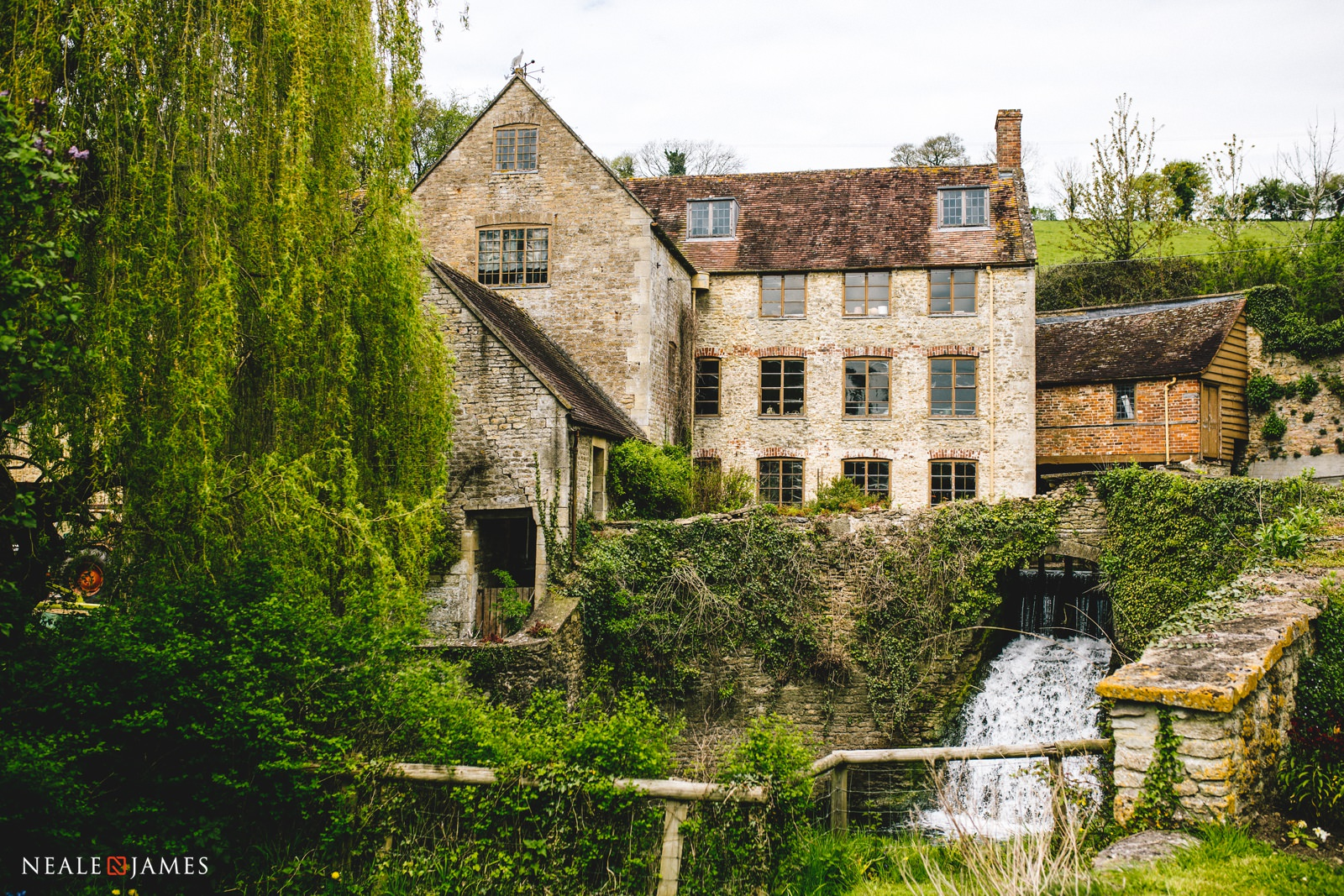 Romantic riverside wedding venue Gants Mill in Somerset nestles in to the hillside with water cascading from the waterwheel