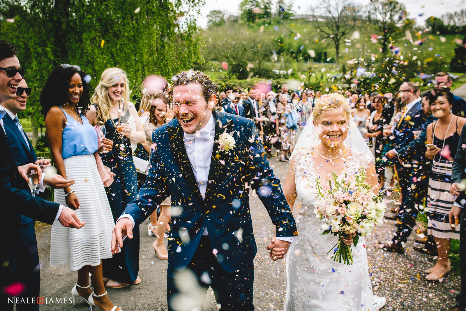 A bride and groom laugh as they're showered with confetti at Gants Mill in Somerset