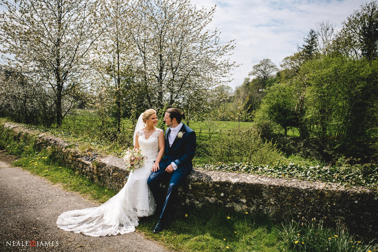 A bride and groom sit together on an old stone wall in the idyllic grounds of Gants Mill in Somerset