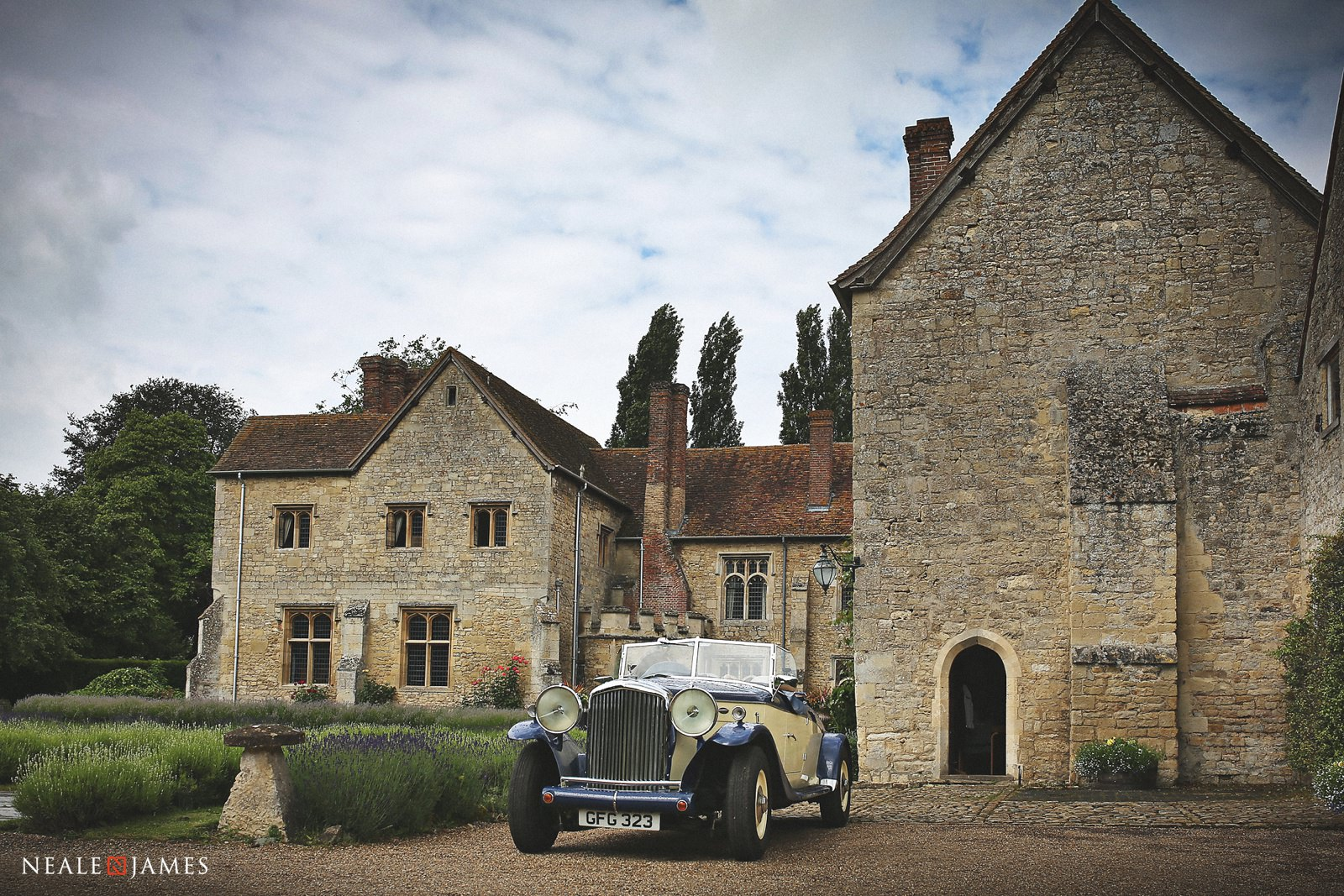 Vintage car outside Notley Abbey with white fluffy clouds in the sky