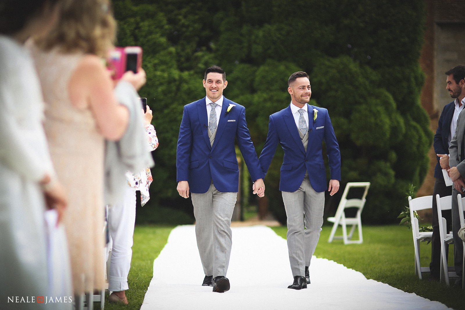 Two grooms in blue jackets and grey trousers walk down the aisle at their summer wedding ceremony at Notley Abbey