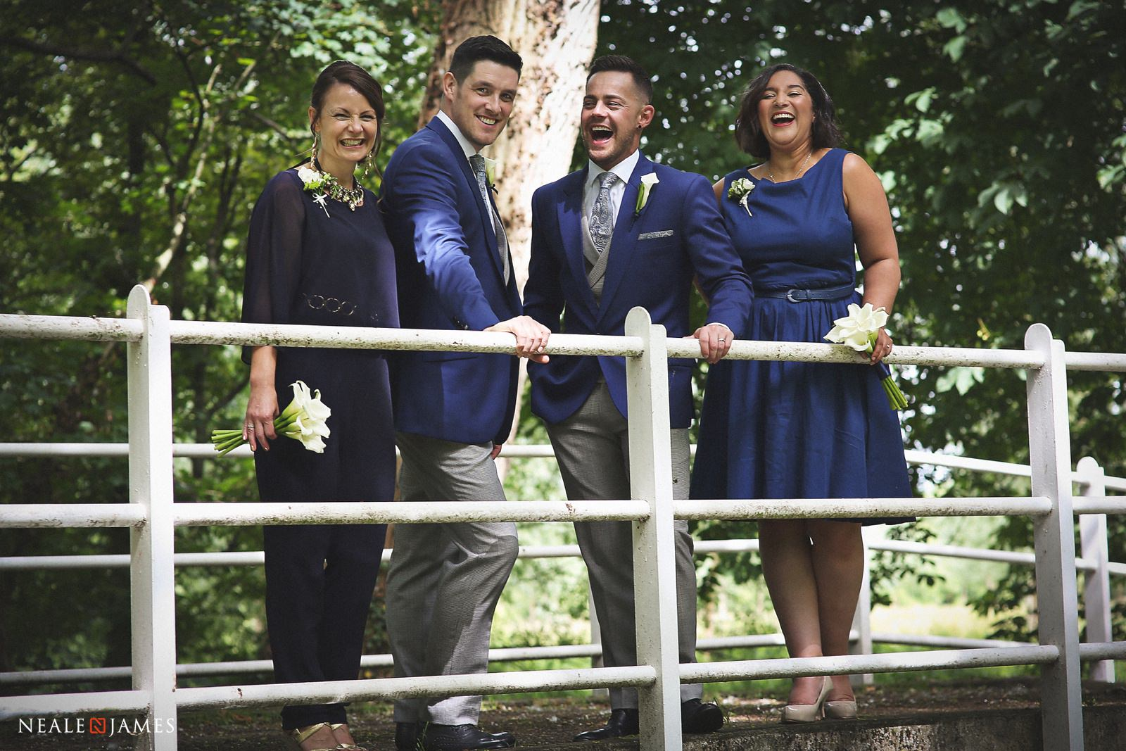 The bridal party stand together on a bridge in the gardens of Notley Abbey