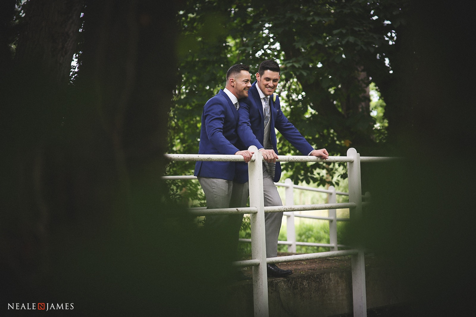 Two grooms stand together on a bridge at Notley Abbey after their outdoor ceremony