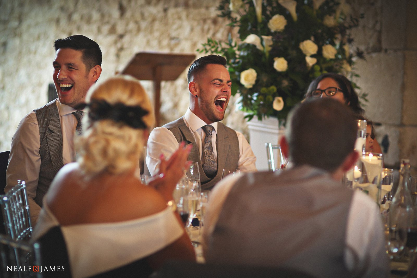 A groom laughs heartily during the wedding speeches at Notley Abbey