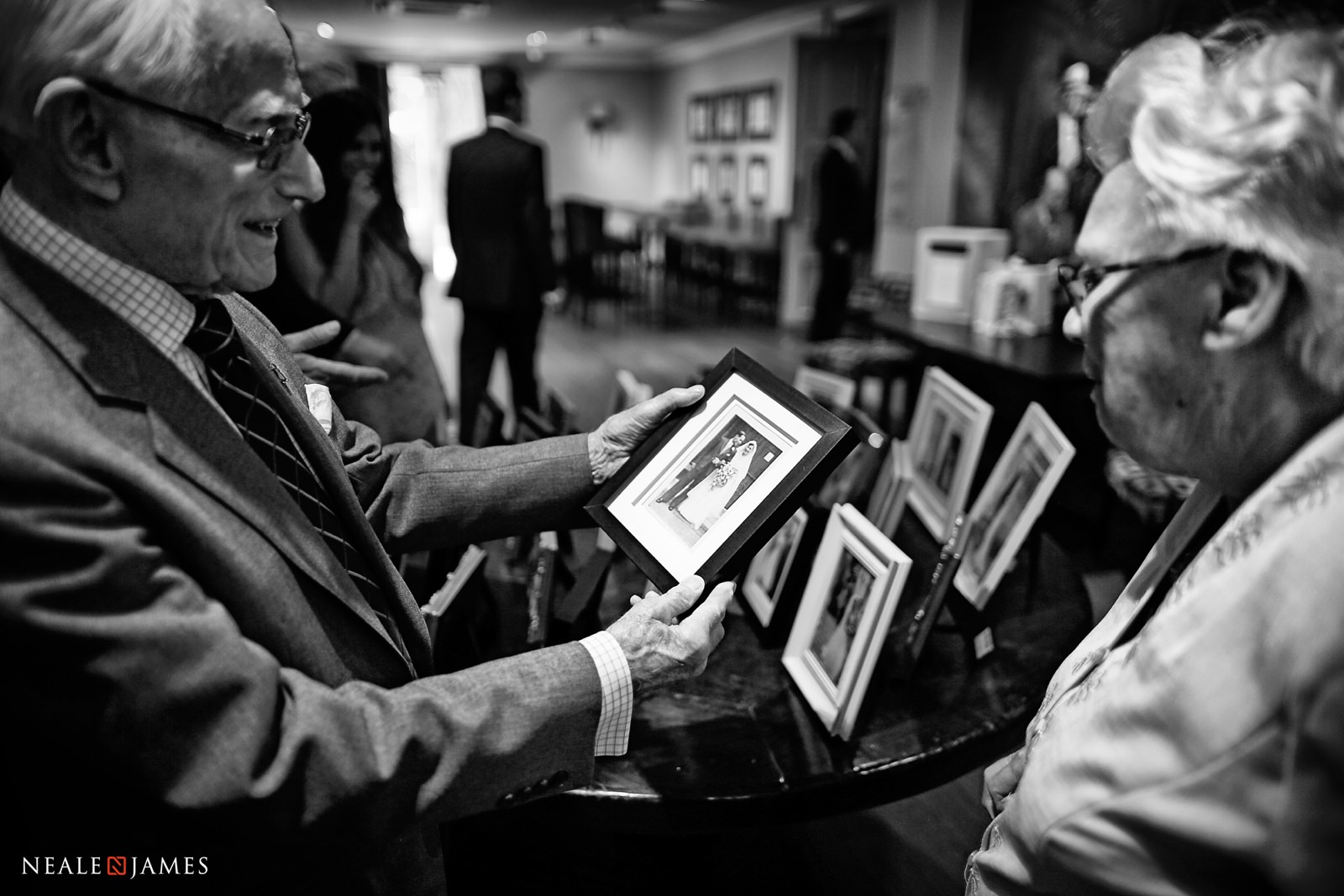 Black and white picture of grandparents looking at an old photo from their own wedding day
