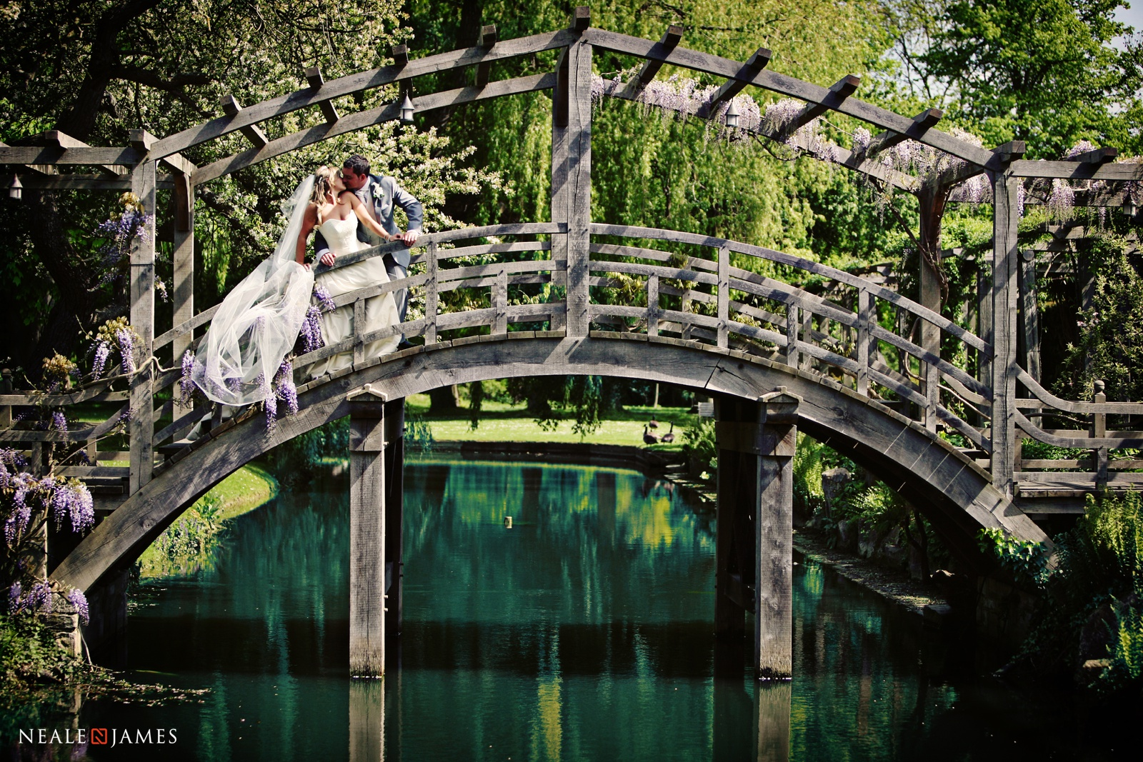 A couple kissing on a bridge at Great Fosters wedding venue