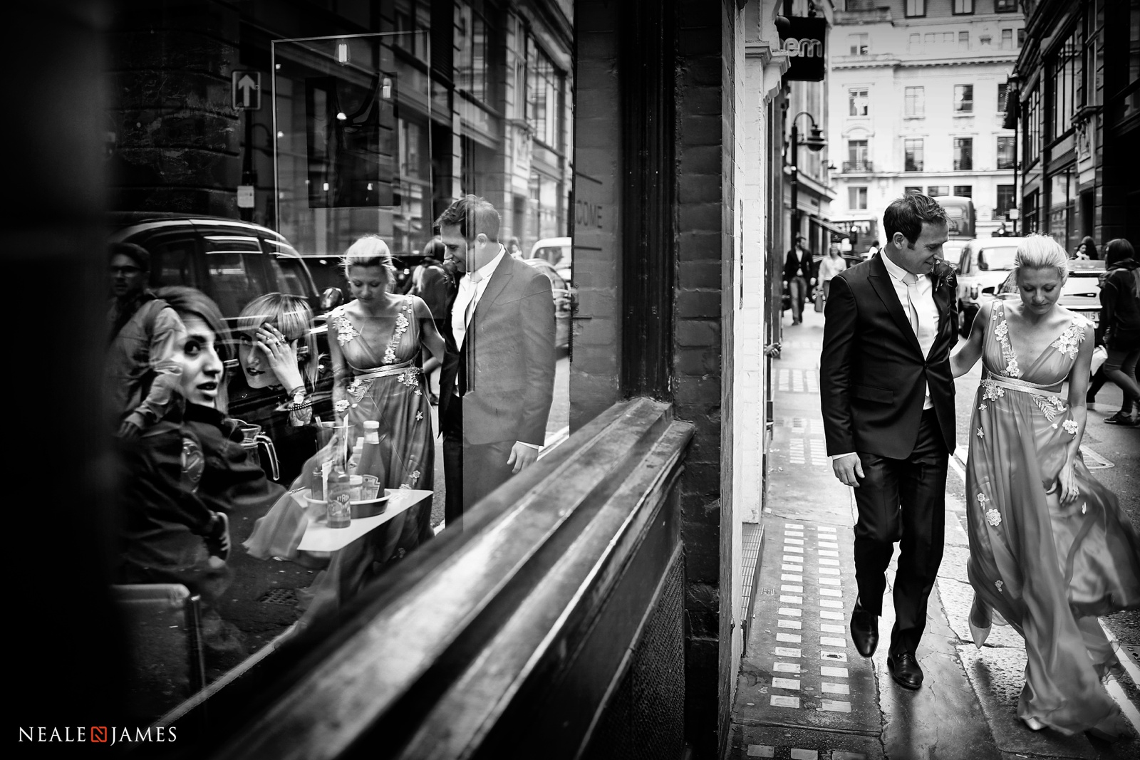 Black and white photograph of a couple walking in London on their wedding day