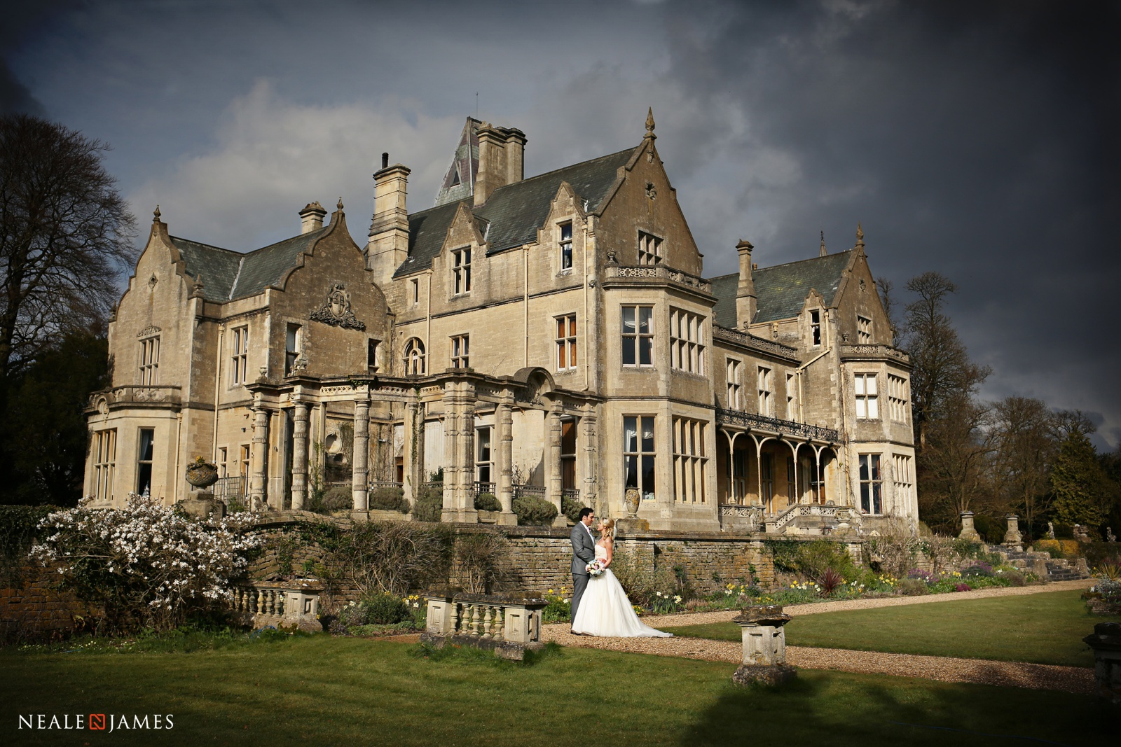 A couple standing in front of Orchardleigh House on their wedding day