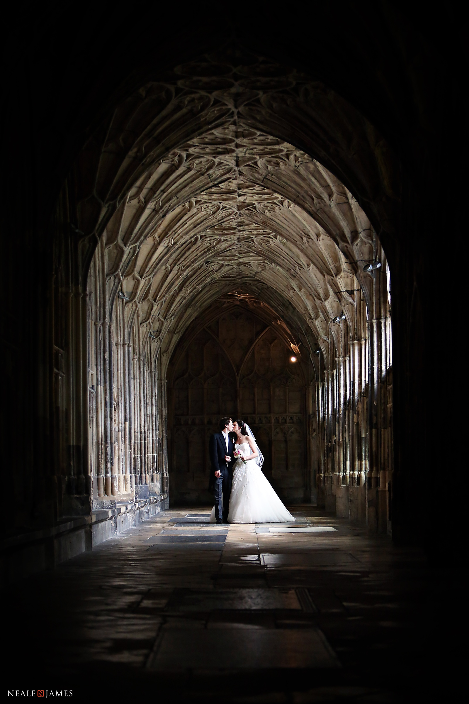 A bride and groom walking through the cloisters at Gloucester Cathedral on their wedding day
