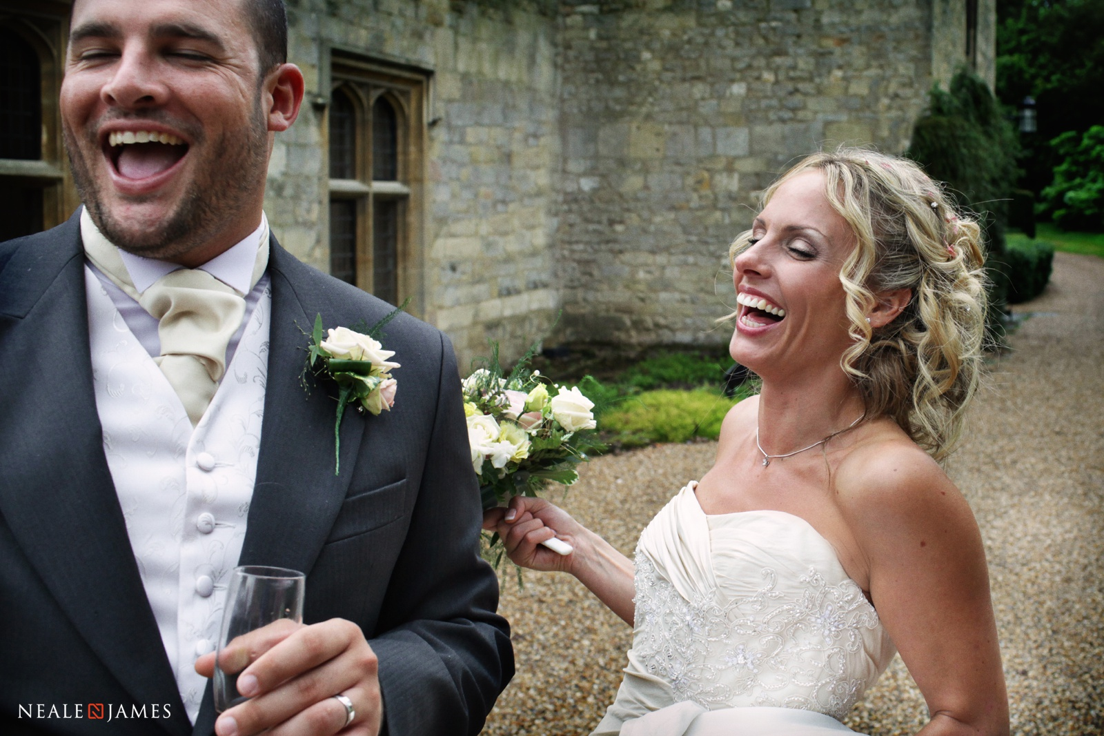 A photograph of a Notley Abbey wedding where the couple are laughing