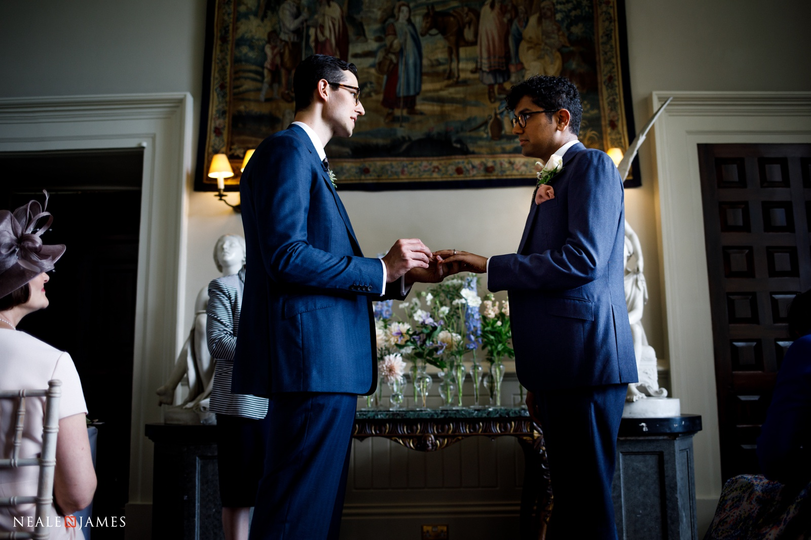 Colour photograph of two grooms exchanging rings at Elmore Court