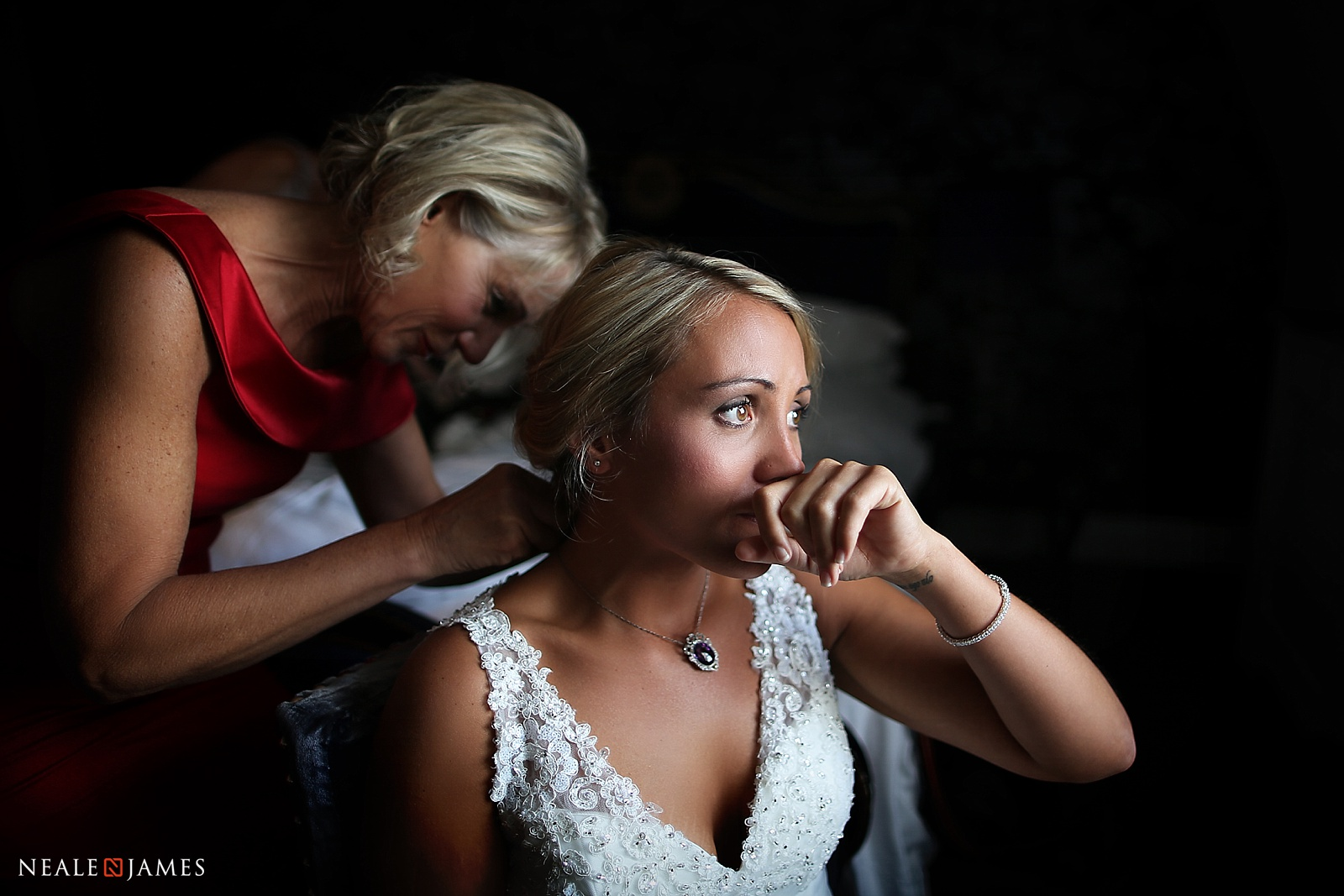 A colour photo of a bride during the last moments of make up, receiving jewellery