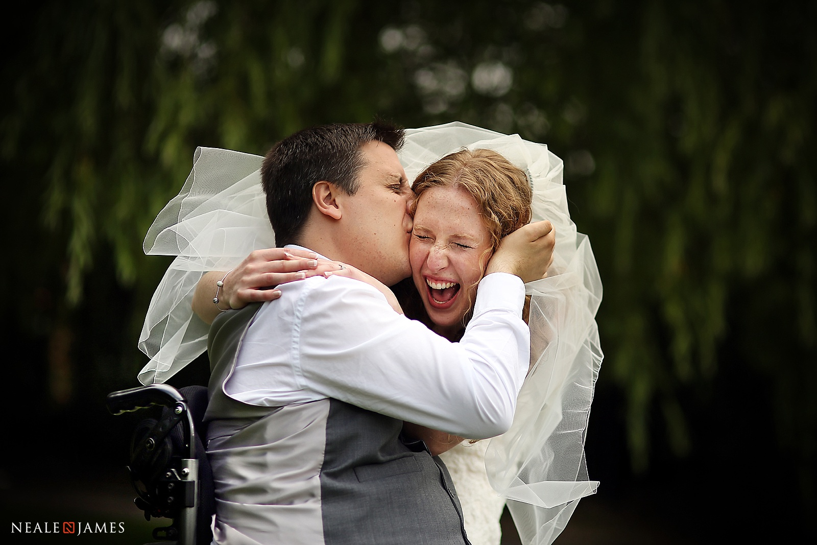 A colour picture of bride and groom laughing on their wedding day