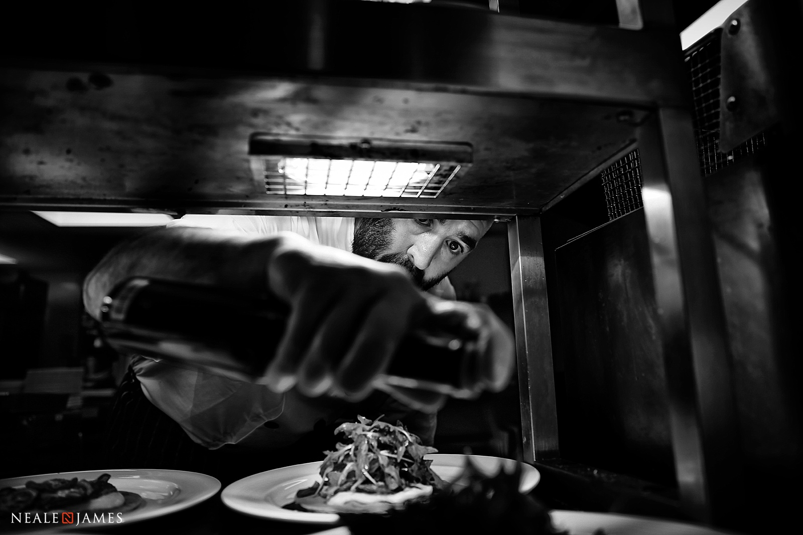 A black and white photo of a chef at Wasing Park wedding venue in Berkshire preparing the main dish
