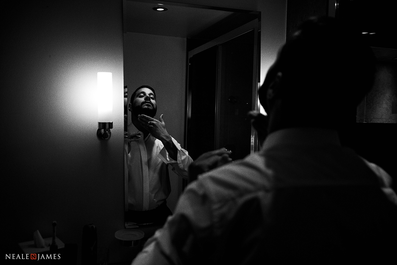 Black and white picture of a groom preparing in the mirror for his wedding at Stoke Place