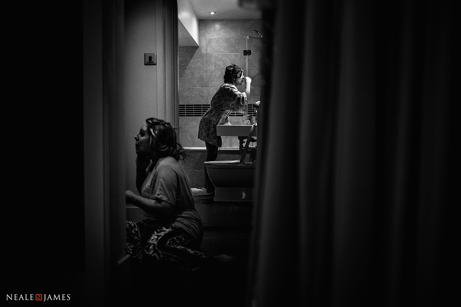 A black and white photograph of two bridesmaids applying make up in a mirror