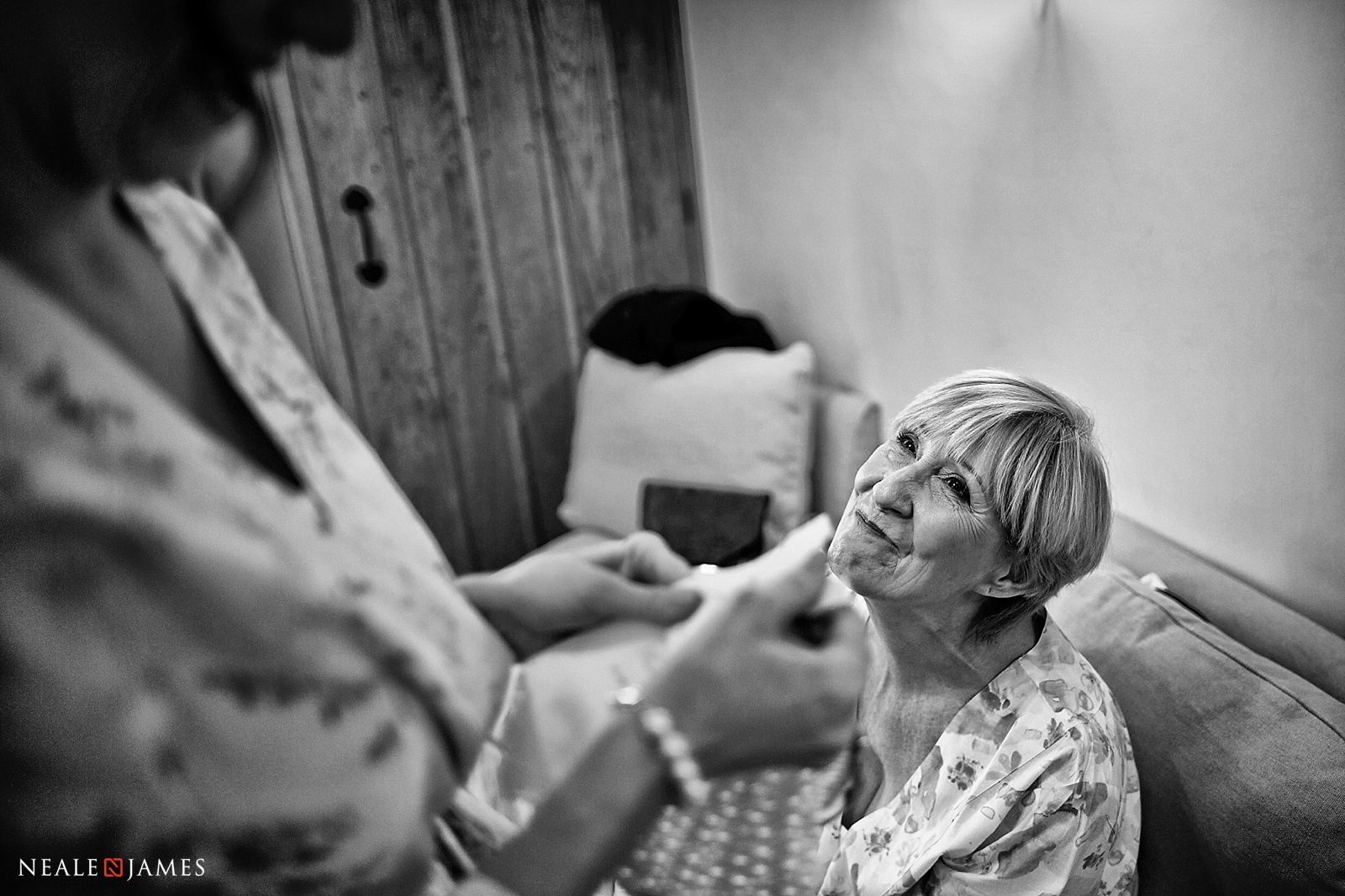 A black and white picture of a mother staring at her daughter on her wedding day