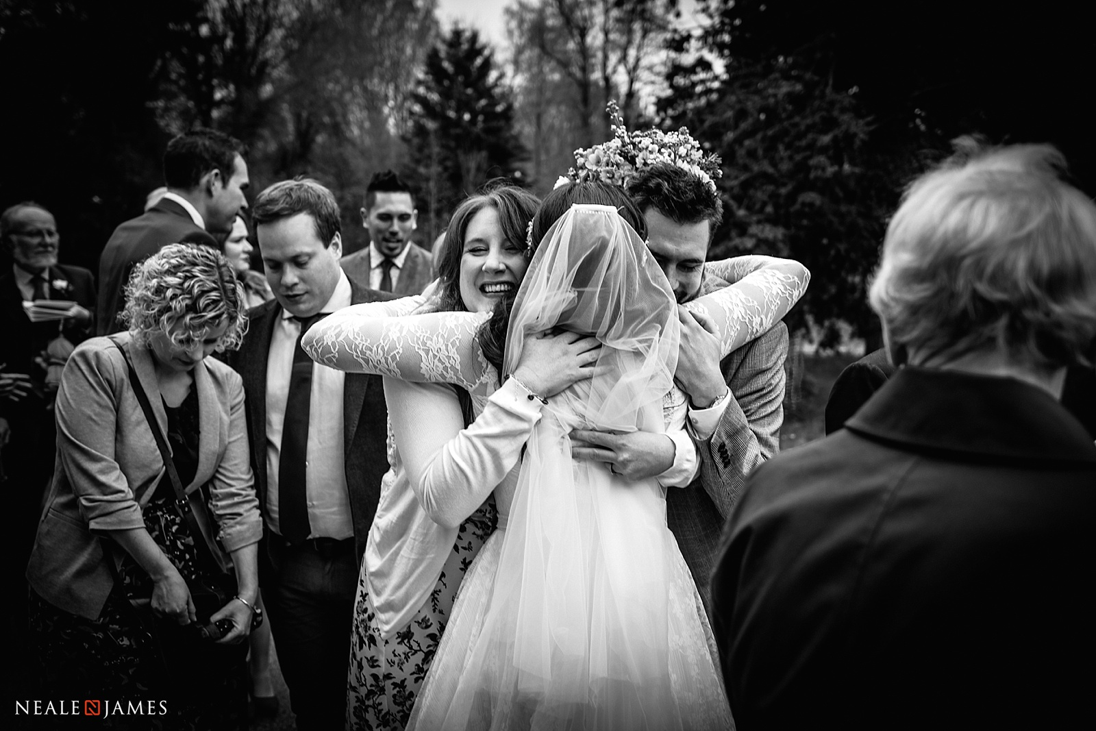 A black and white photograph of a bride hugging guests outside Shaw Church in Newbury