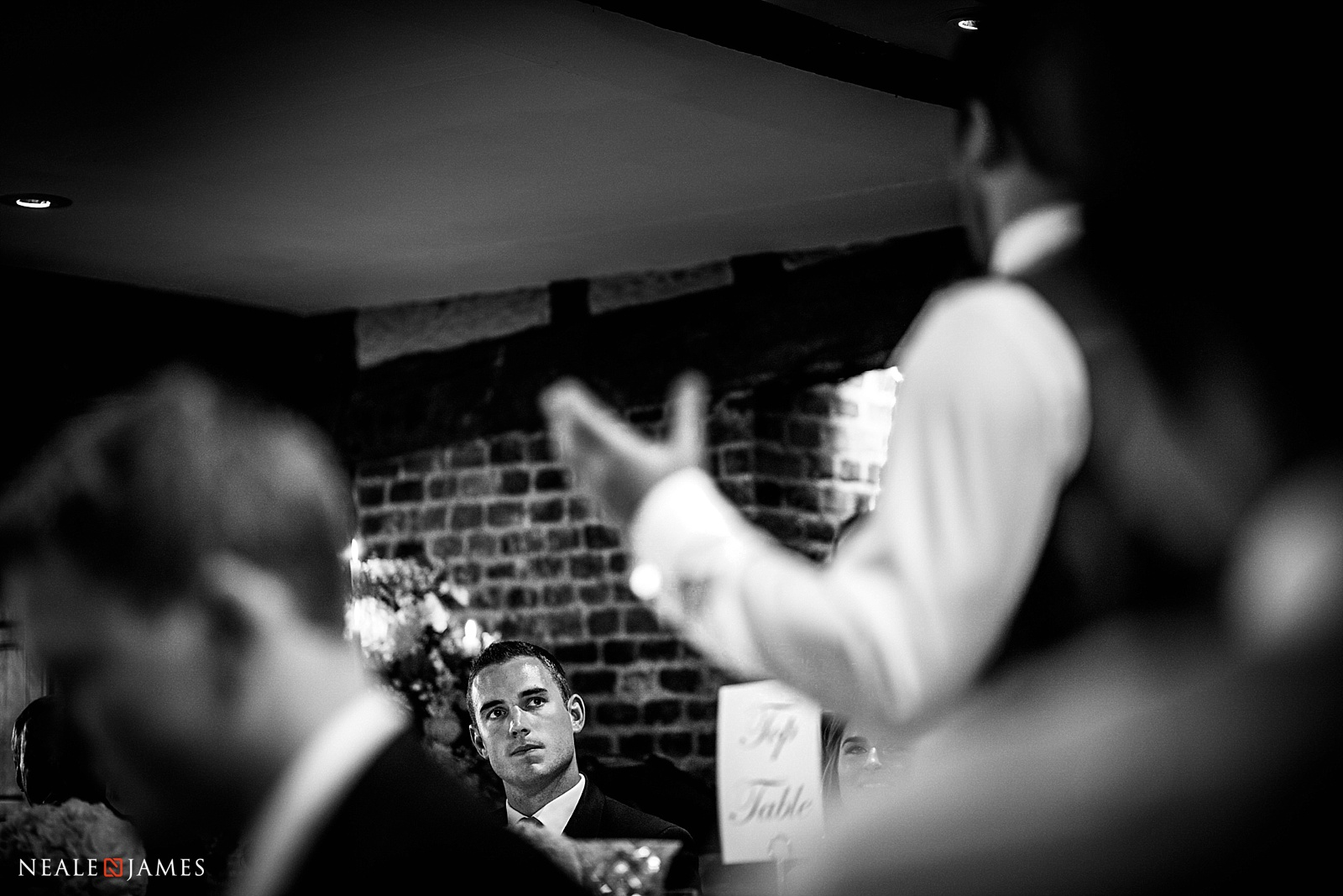 Black and white photo of a wedding speech from unusual camera angle