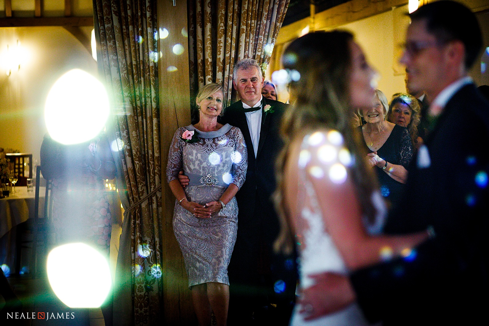 A colour photo of mum and dad watching on as the bride and groom have their first dance
