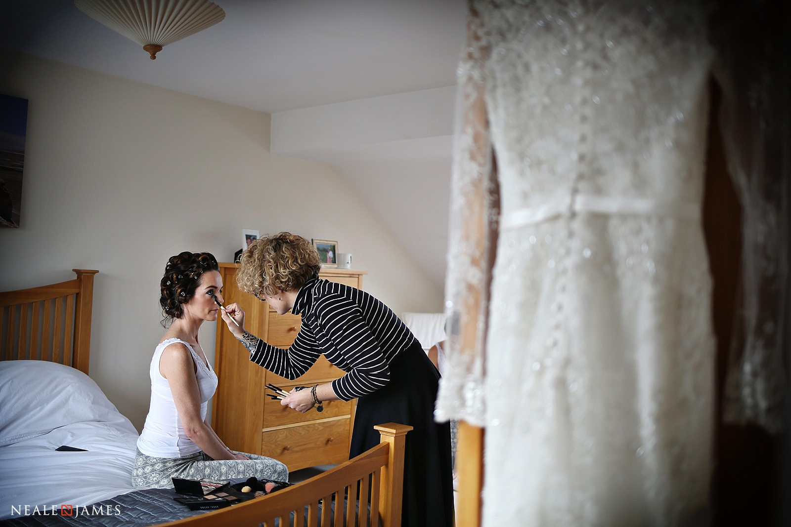 Colour photograph of a bride having make up applied with her dress in the foreground