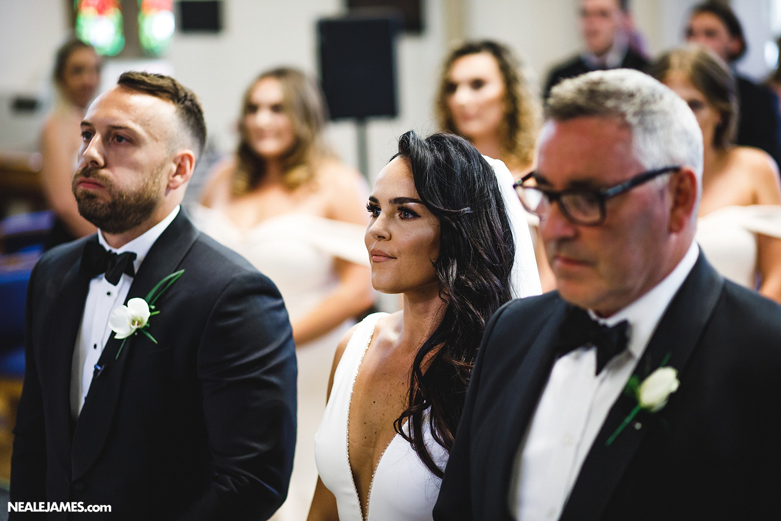 Colour picture of the moment a groom realises the significance of the day standing before the alter with his wife