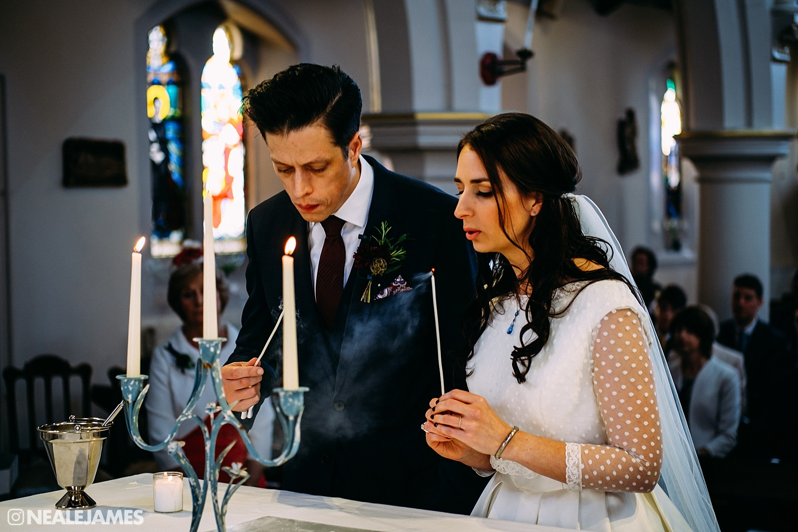 A bride and groom light a unity candle in Sacred Heart Church Gosport