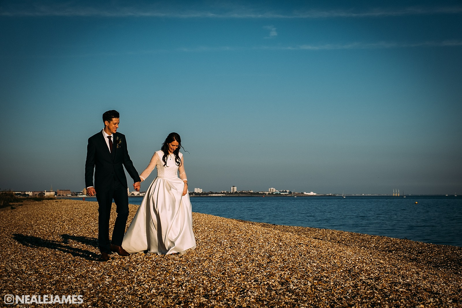 A colour photograph featuring a couple walking on the beach in Gosport, Portsmouth