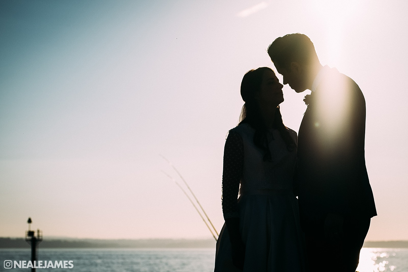 A silhouetted colour picture of a couple on their wedding day on Gosport beach