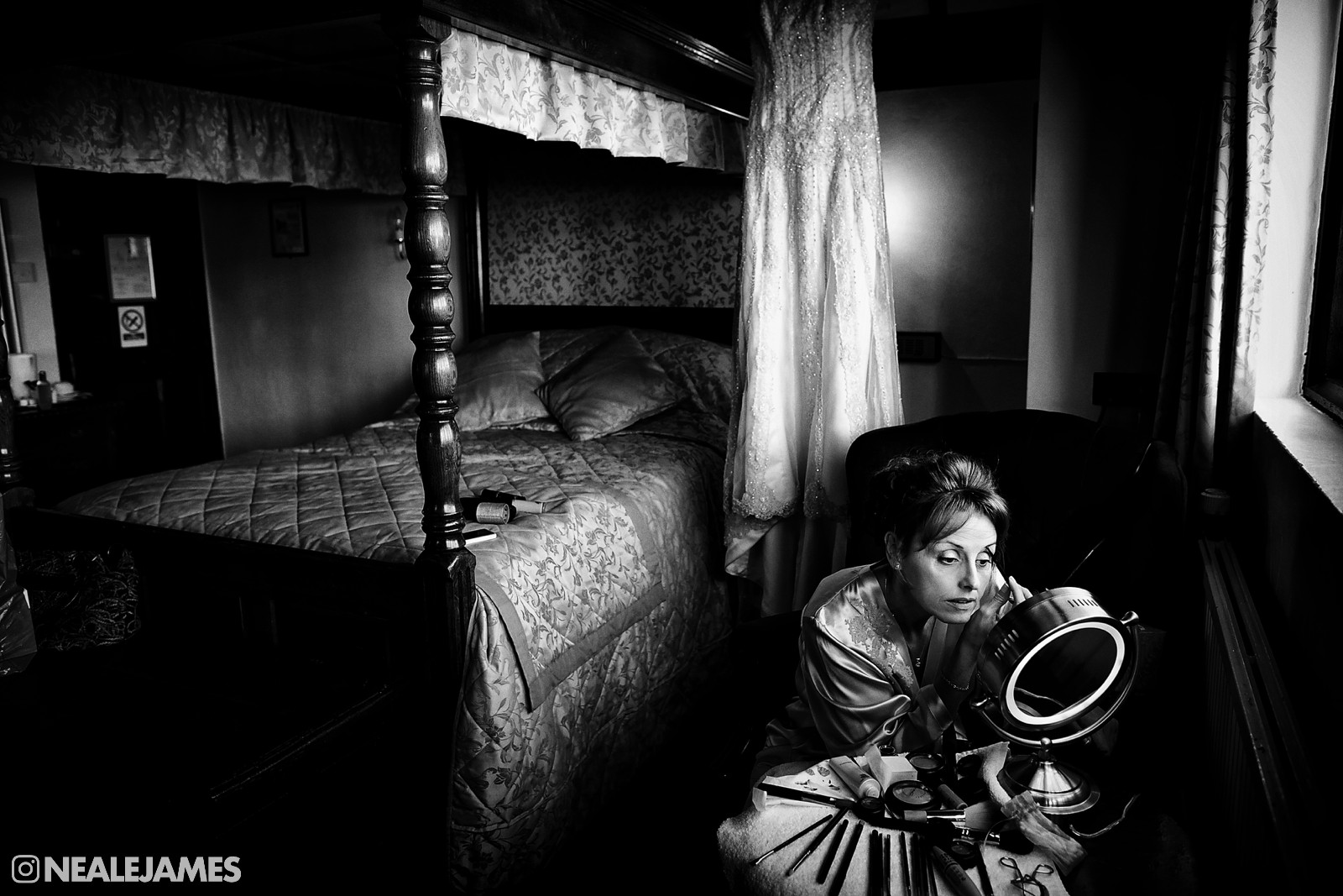 A black and white image of a bride applying makeup, illuminated by window light only