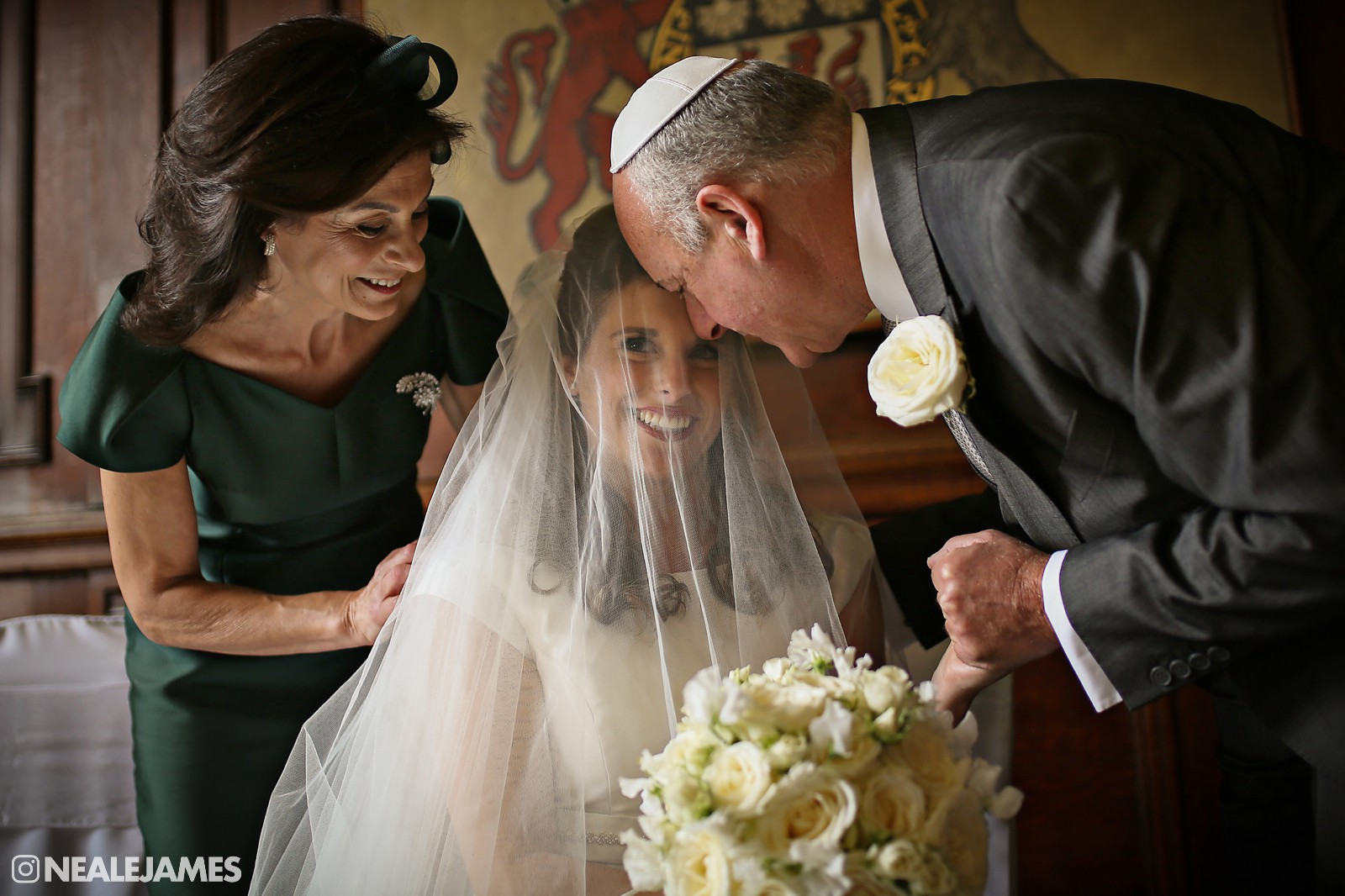 A bride spends moments with her mother and father just prior to her Jewish wedding celebrations