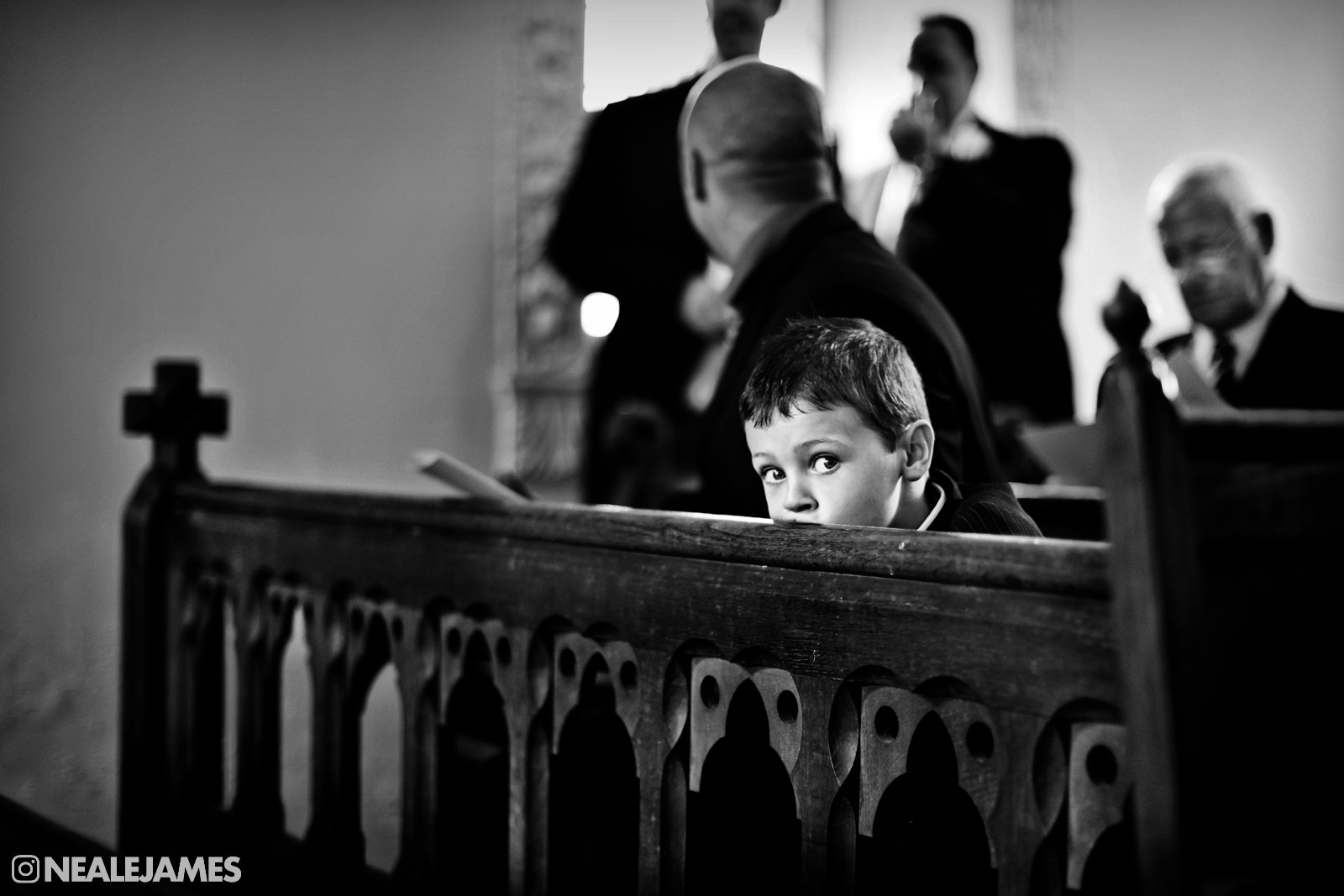 Black and white photo of a boy waiting for a wedding ceremony to start