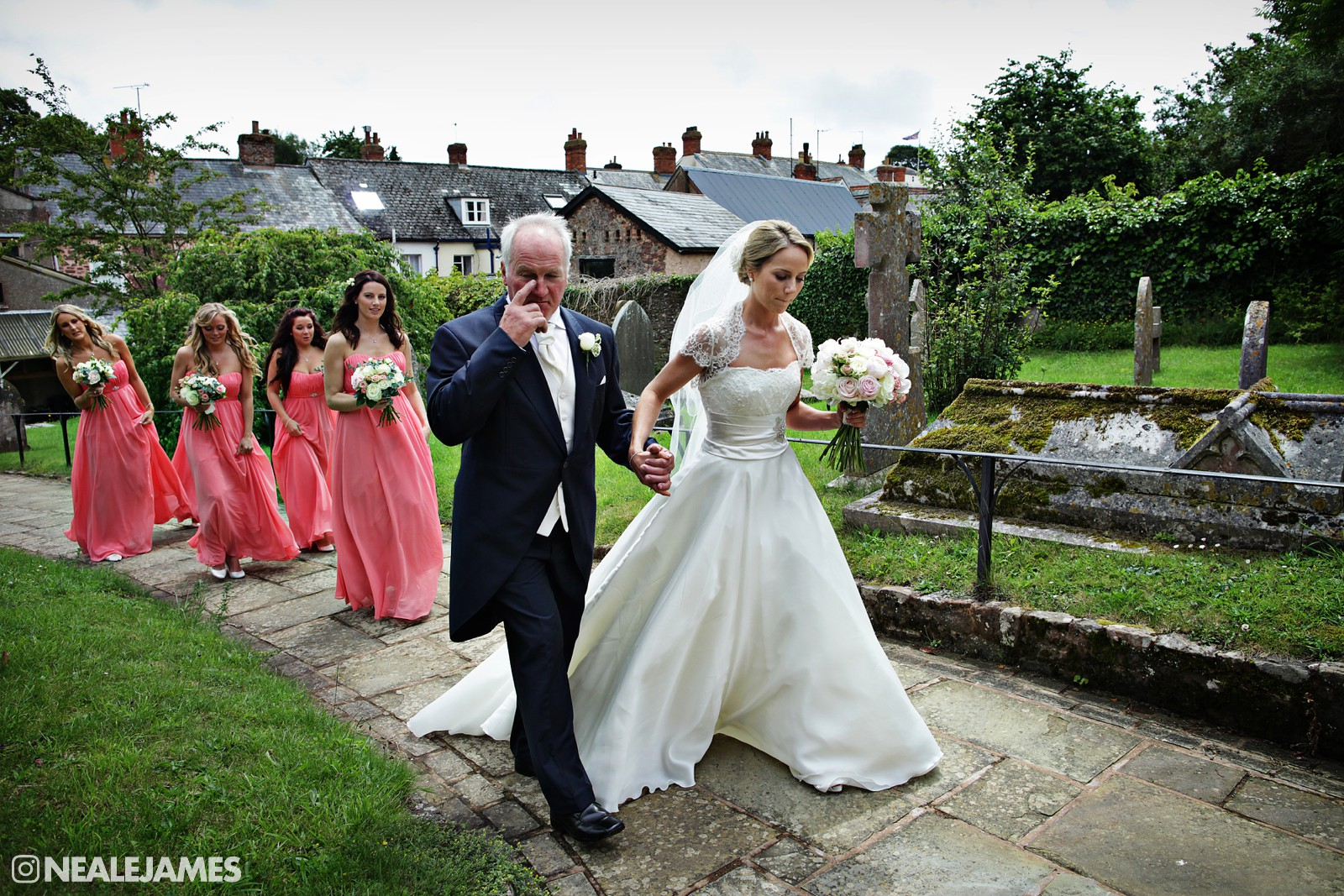 Colour photo of a bride arriving at church with her father