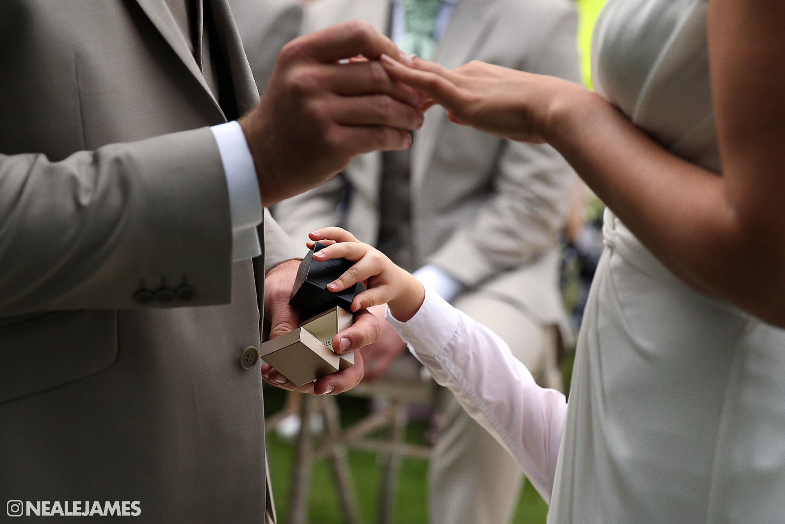 Picture of a boy reaching up to pass a groom the wedding ring