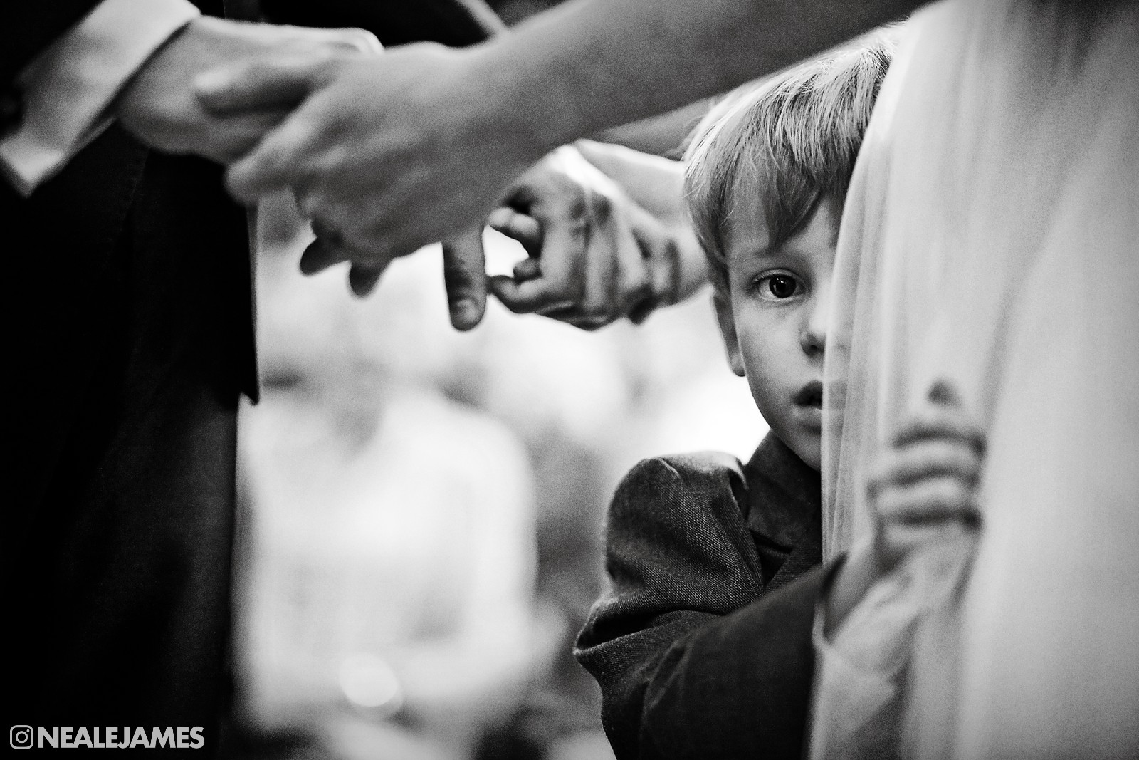 Black and white wedding picture of a young lad looking around his mother's wedding gown