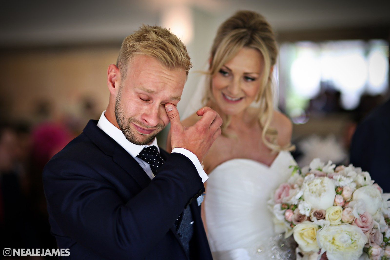A groom wipes a tear from his eye in this picture, as his new wife watches on