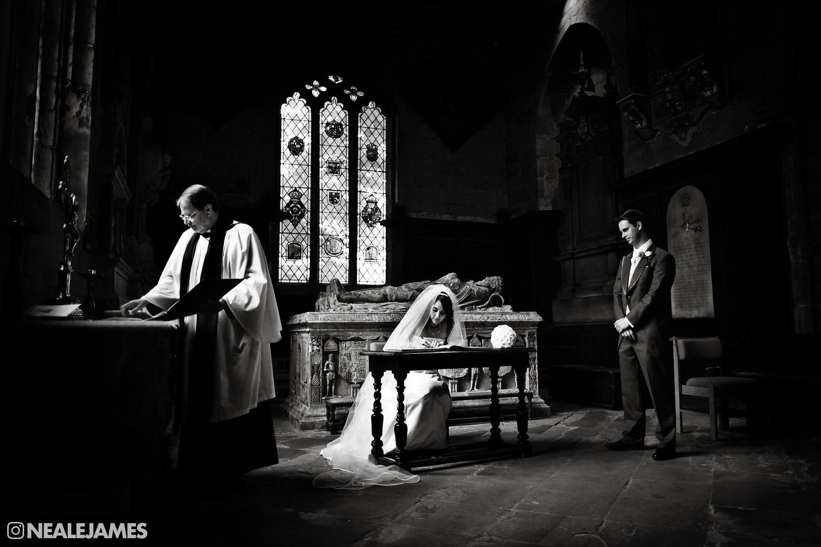 Black and white photograph of bride and groom signing the register at the alter in an English church
