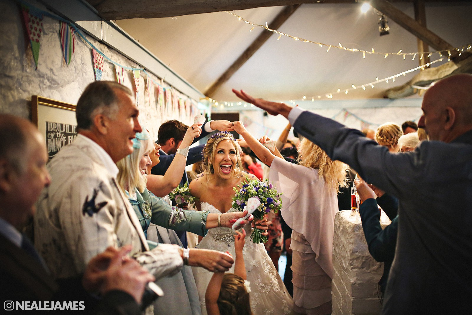 A bride and groom making their way through an indoor confetti run