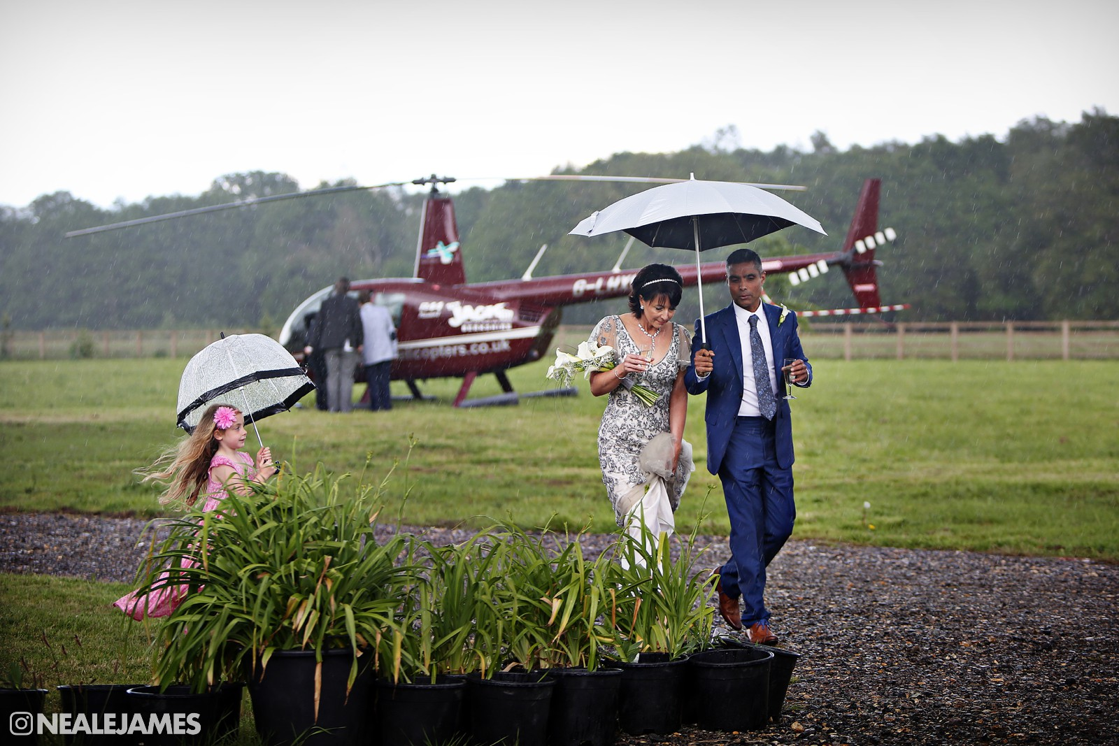 Colour photograph of a helicopter arriving at a wedding with bride and groom