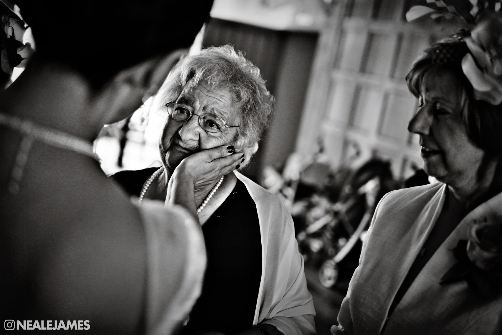 A black and white wedding photo of a mother and daughter in emotional exchange after a wedding