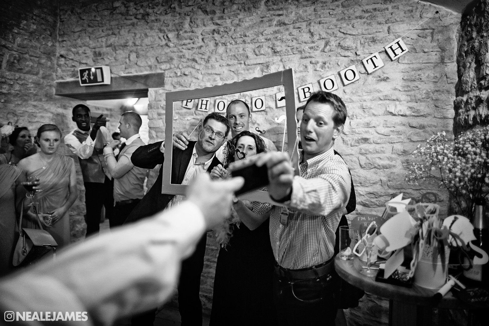 A black and white picture of guests at a wedding in a mobile photo booth