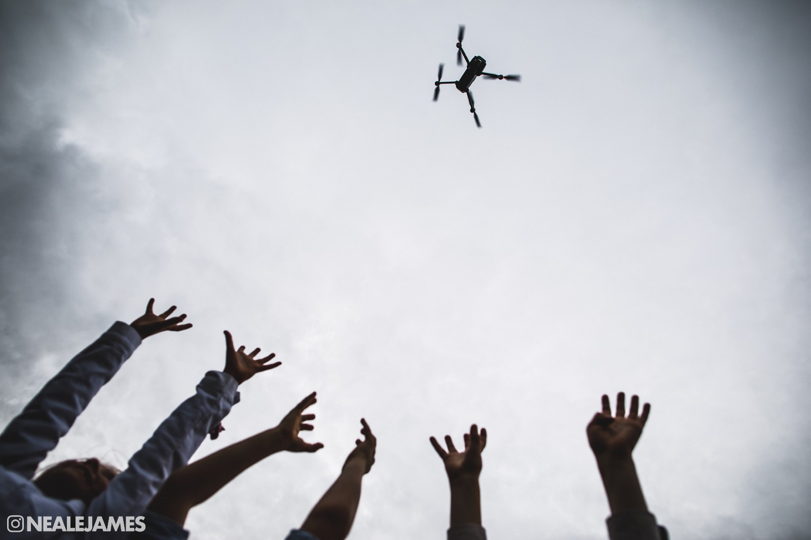 Hands reaching out to a drone in the sky at a wedding